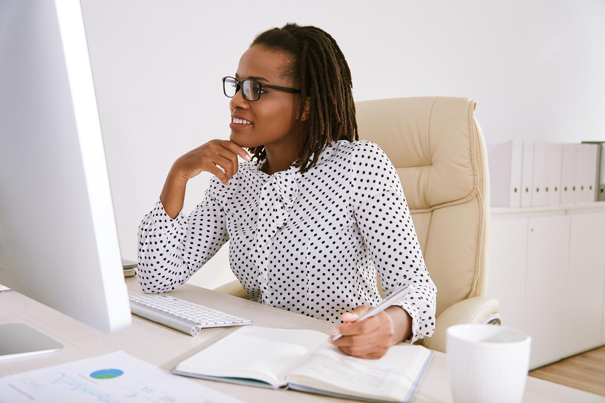 African-American business executive reading data on computer screen and taking notes